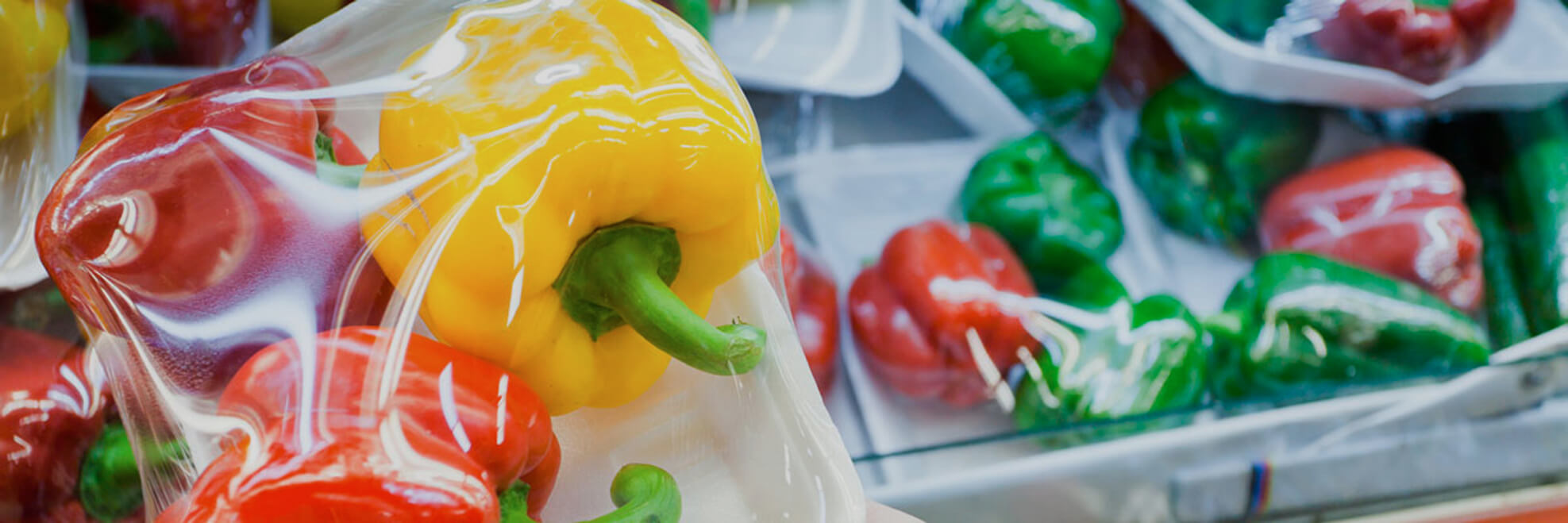 shrink wrapped red, yellow and green peppers