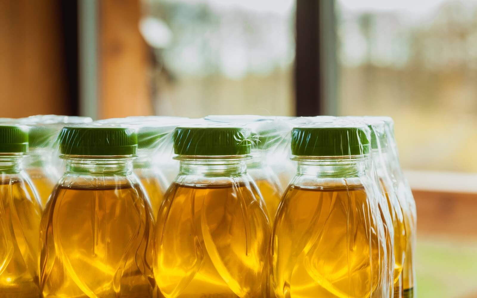 shrink wrapped bottles of yellow liquid and green tops